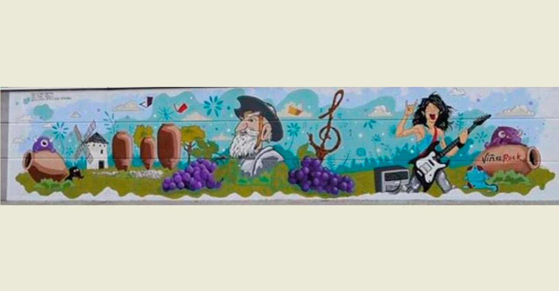 Alumnos de los institutos finalizan el grafiti que decora el pabellón deportivo del colegio Virgen de la Caridad.